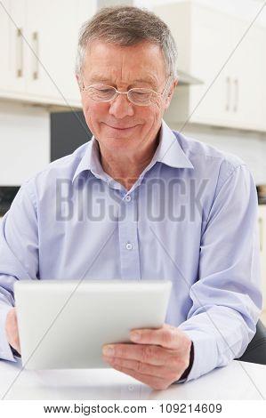 Senior Man Using Digital Tablet At Home