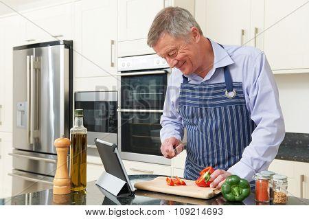 Senior Man Following Recipe On Digital Tablet