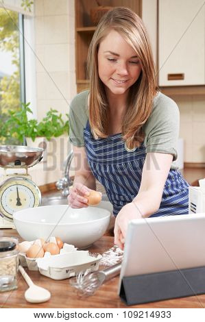 Woman Baking And Following Recipe On Digital Tablet