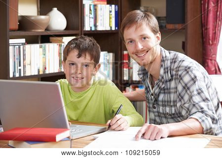Boy Working At With Tutor At Home