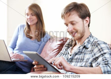 Couple Using Digital Technology At Home