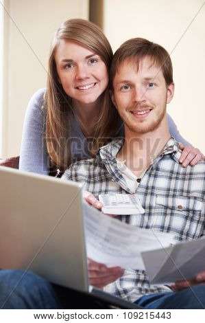 Happy Young Couple Looking At Finances On Laptop