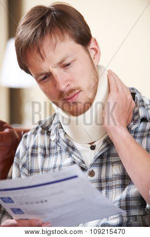 Man Wearing Surgical Collar Reading Letter