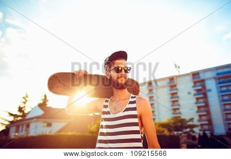 Man In Sunglasses With A Skateboard On A Street In The City At Sunset Light