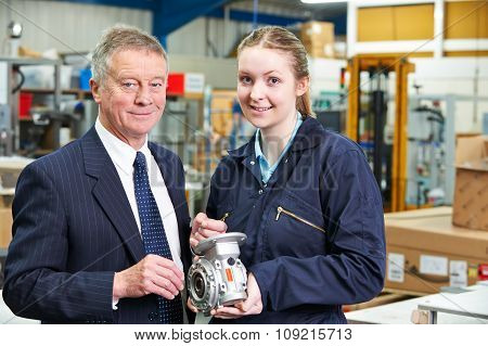 Portrait Of Manager And Apprentice Engineer Inspecting Component