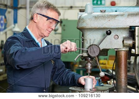 Skilled Engineer Using Drill In Factory