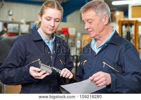 Apprentice Engineer Measuring Component With Micrometer