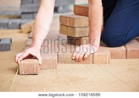 Man Laying Blocks For Patio