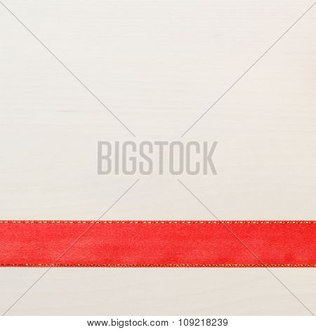 Red Ribbon On Bright Wooden Surface With Copy Space.