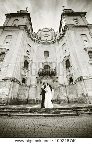 Happy Wedding Couple Outdoor With Old Building Behind