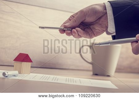 Closeup Of Male Hands Holding A House Key And A Pen Over A Contract Of House Sale