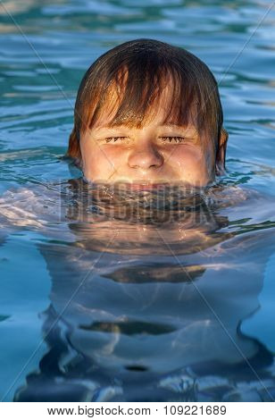 Child Swims In The Outdoor Pool