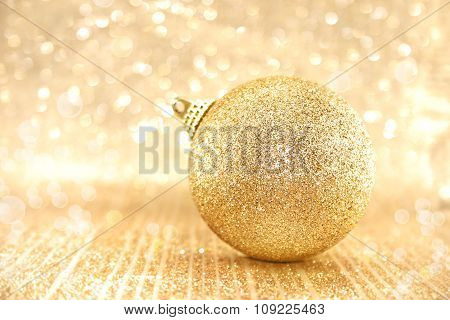 Golden Christmas Ball On Shiny Background With Copy Space For Text. Selective Focus