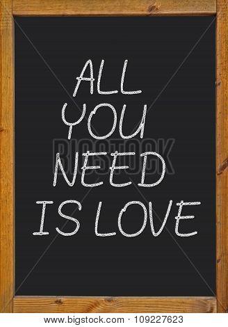 All you need is love written on a blackboard