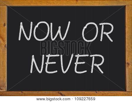 Now or never written on a blackboard