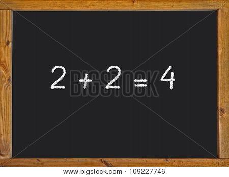 2 + 2 = 4 written on a black blackboard