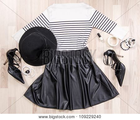 Striped Blouse And Leather Skirt With Accessories Arranged On The Floor.