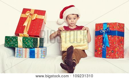 boy in red santa helper hat with gift boxes - christmas holiday concept