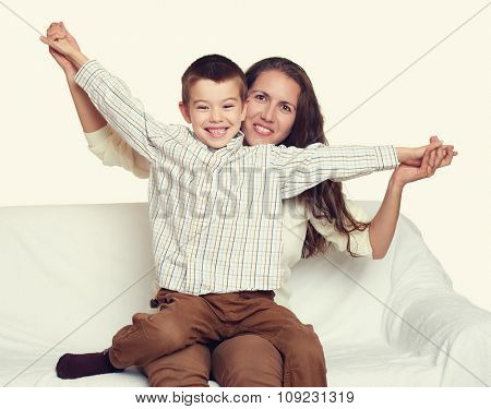woman with child boy portrait sitting on sofa and playing