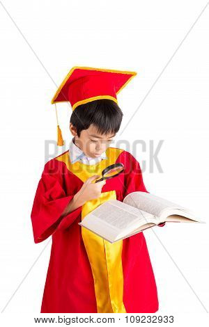 Portrait Of Curious Boy In Red Gown Kid Graduation With Mortarboard Looking A Book Through Magnifyin