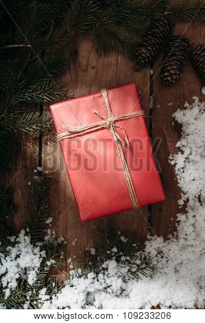 red gift box and fur tree on wooden background