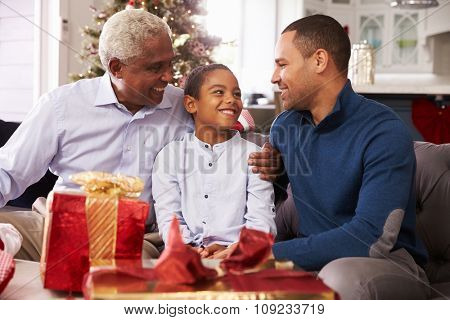 Grandson With Grandfather And Father Opening Christmas Gifts