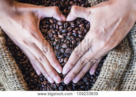 Closeup Coffee Beans In Hands Of Heart Shaped With Sunlight In Gunny Bag. I Love Coffee
