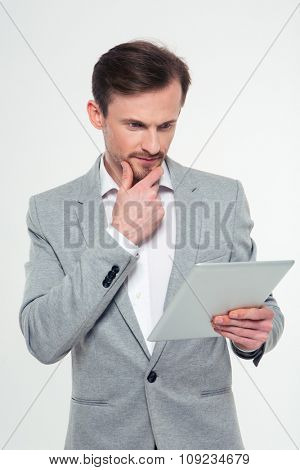Portrait of a thoughtful businessman using tablet computer isolated on a white background