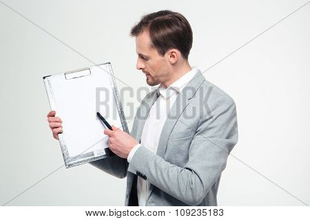 Portrait of a young businessman showing blank clipboard isolated on a white background
