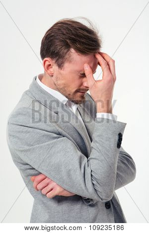 Portrait of a pensive businessman standing isolated on a white background