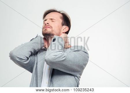 Portrait of a young businessman having neck pain isolated on a white background