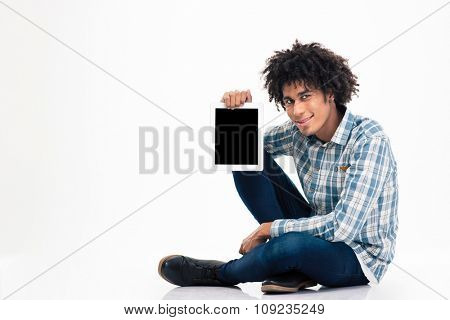 Smiling afro american man sitting on the floor and showing blank tablet computer screen isolated on a white background