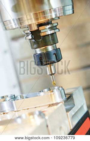 Milling machine tool with mill in chuck preparing to process metal detail at industrial manufacture factory