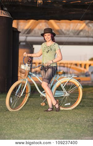 Young Lady Standing With A Bike At Sunset