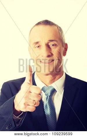 Smiling mature businessman gesturing ok sign.