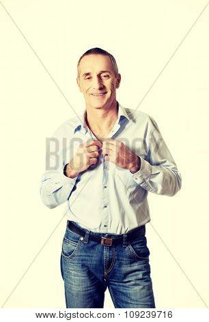 Handsome mature man buttoning his shirt.