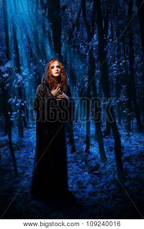 Young witch at night forest
