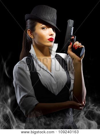 Portrait of young woman in manly style with gun and smoke