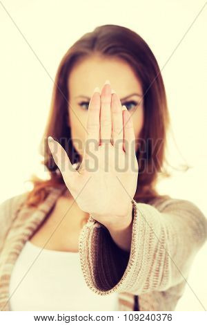Beautiful casual woman making stop gesture.