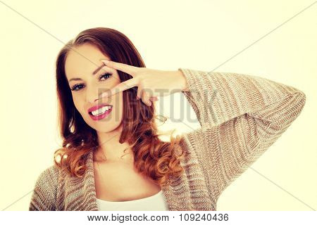 Casual smiling woman showing peace gesture.