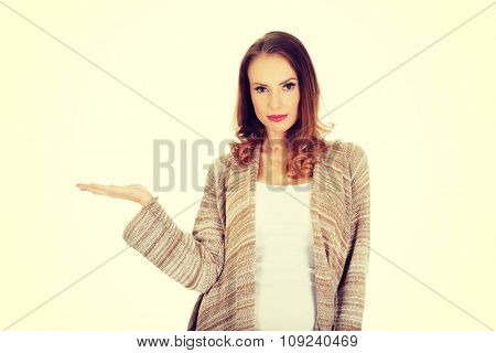 Beautiful casual woman showing empty hand.