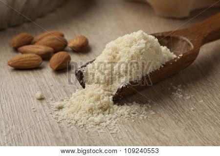 Wooden spoon with almond meal and almonds