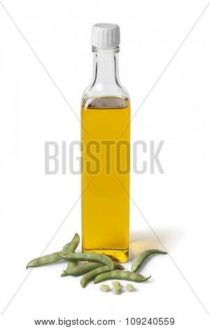 Bottle of soybean oil and fresh soy beans on white background