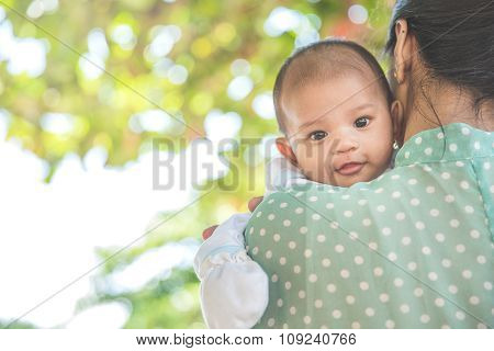 Woman Holding Her Baby Daughter, Baby Looing At The Camera