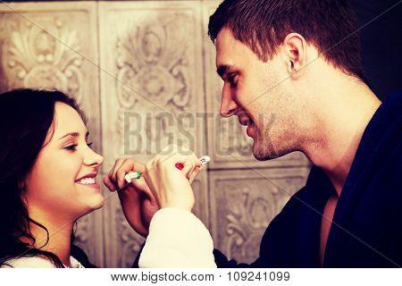 Beautiful couple in the bathroom brushing teeth.