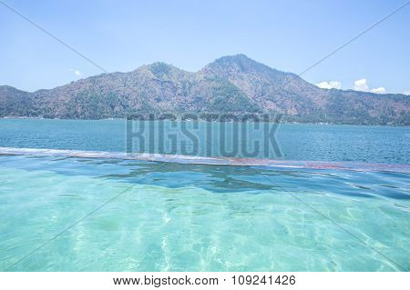 Infinity Pool With Lake And Mountain At The Background