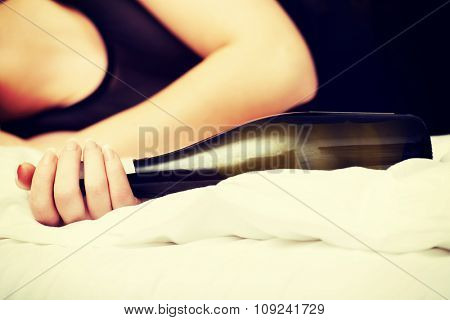 Drunk woman sleeping on bed with bottle of wine.