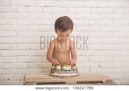 Cute Caucasian Boy Playing With His Birthday Cake