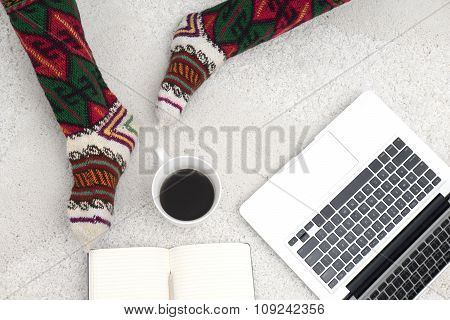 Shot Of Woman Feet, Laptop, Coffee And Notebook On The White Carpet