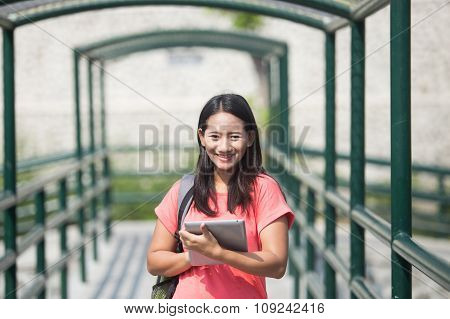 Young Asian Student In Her Outdoor Activity, Standing And Holding A Tablet Pc